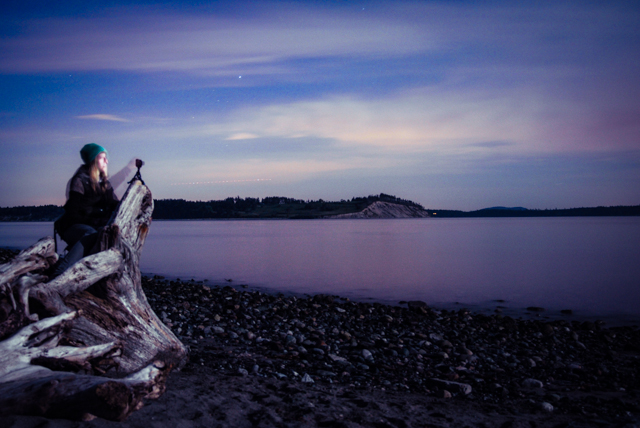 Nicole rests her tripod and camera upon a piece of stumpish driftwood with James Island in the background
