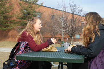 Freshmen Rhiannon Parise, left, and Rebekka Lange, right, soak up the warm weather in between classes outside of the EHS building on Thursday, Feb. 23.