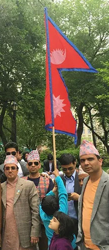 A man holds the flag of Nepal at a parade
