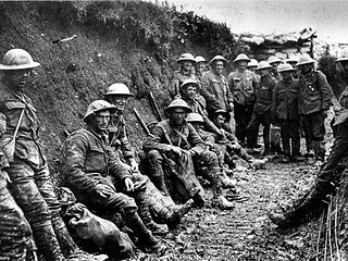 Seventeen soldiers in dirty clothes standing in a trench only a little taller than they are