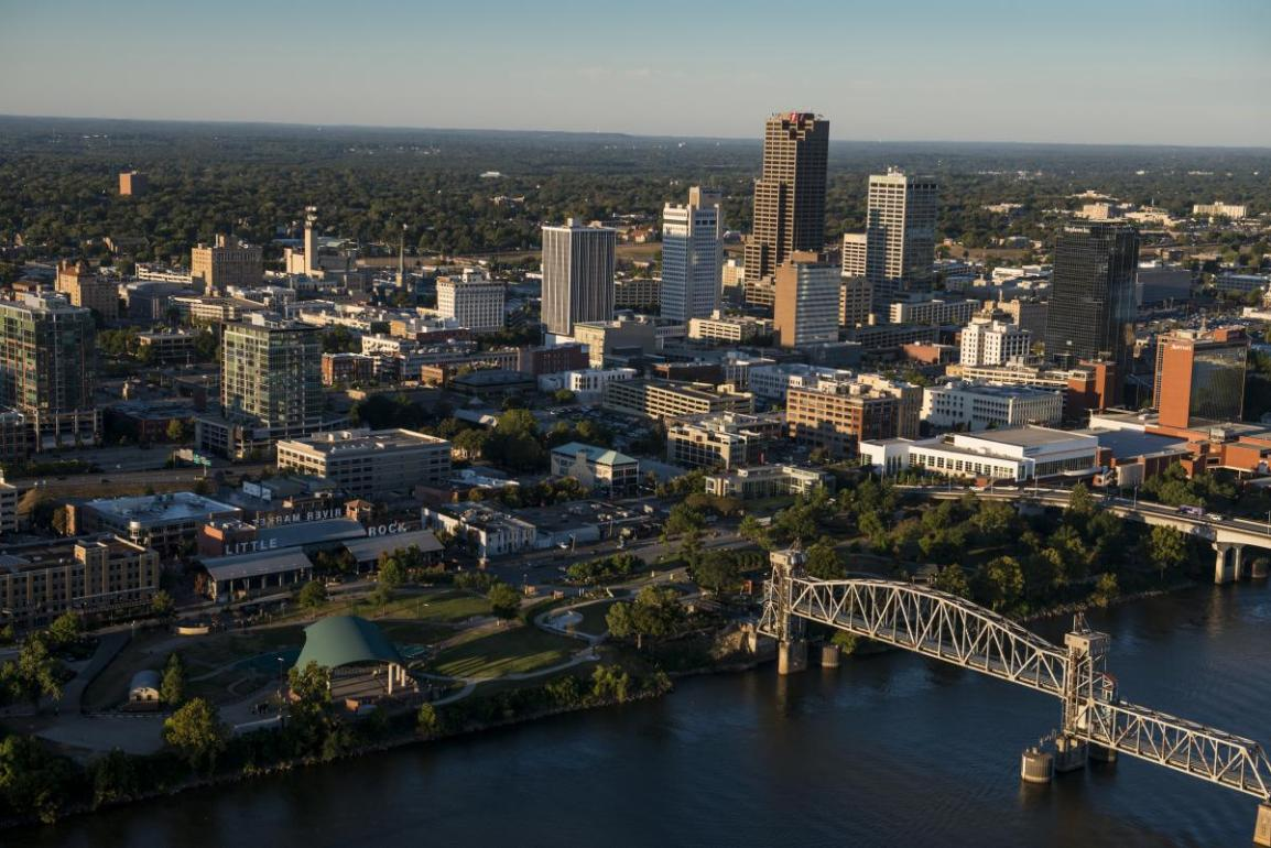 An aerial photo of Little Rock, Arkansas. A metal bridge over a river is in the foreground, skyscrapers are in the middle of the picture and forests in the background.