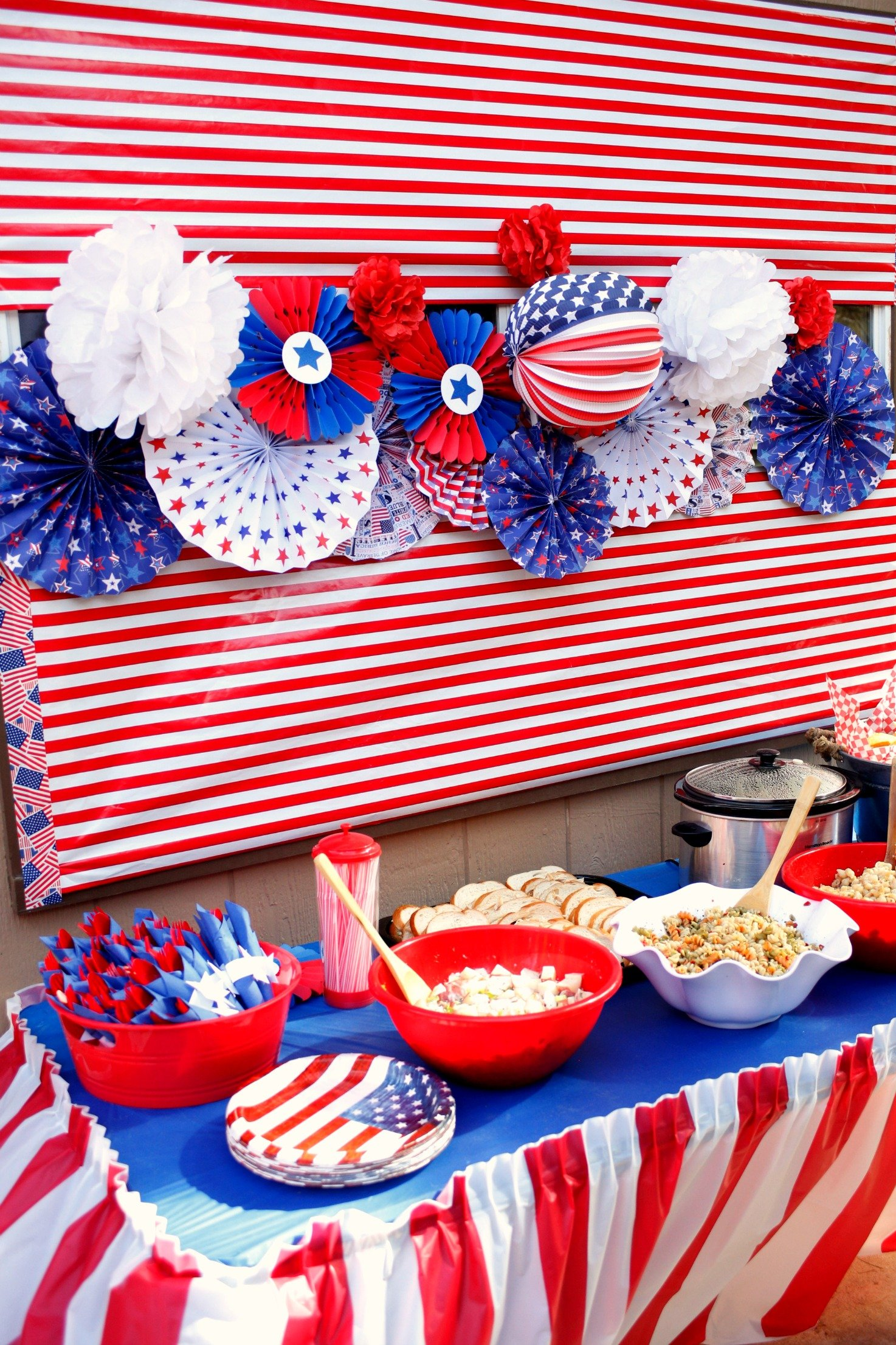 Set up a backdrop for your patriotic buffet with diy rosettes, Dollar Tree decorations and red and white wrapping paper.