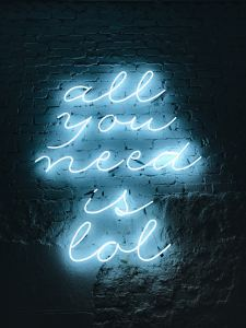 Black wall with blue neon lit sign. If you are looking to find some joy during the hard stuff, you've come to the right place. Laura Jordan believes that finding humor in life is key to growth. email jordan therapy services to find out more.