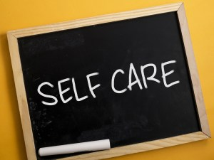 Chalkboard with self care written on it. If you're tired and struggling with postpartum depession in Indiana. We also offer counseling for our Texas residents for postpartum depression in texas. Laura Jordan is happy to serve you at Jordan Therapy Services