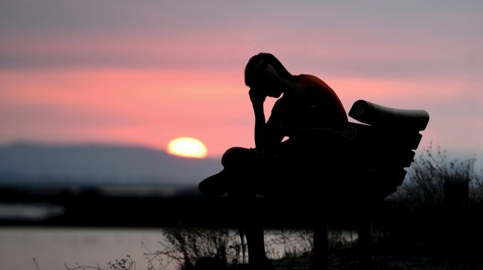 Silhouette Of Woman Sitting On Bench During Sunset