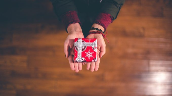 Person Holding Red And White Box