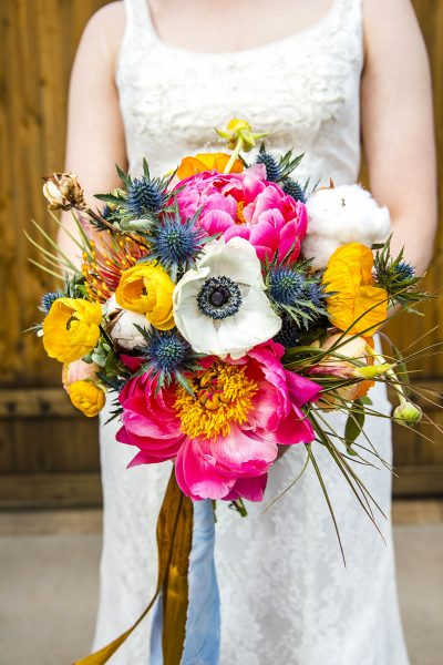 Colorful coral charm peony, ranunculus, and air plant bouquet for west Texas wedding