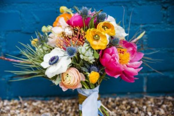 Textured and vibrant bouquet of Coral Charm Peonies, Thistle, Anenomes, Airplants, Succulents, Protea, Poppies, and Ranunculus. Designed by Texas florist Jessica Ormond Events. Captured by Caitlin & Ryan Photography.
