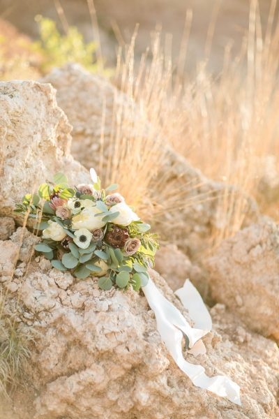 Bridal bouquet designed by Jessica Ormond Events resting on rock and photographed by Allee J.