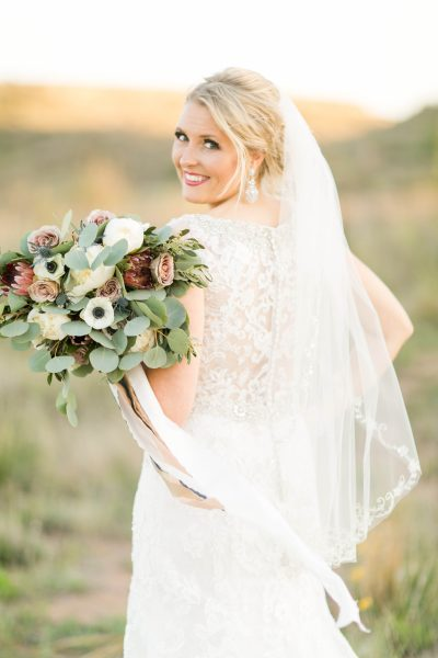 Glancing bride with loose bohemian bouquet. Photo by Lubbock photographer Allee J. Flowers by Texas wedding florist Jessica Ormond Events.