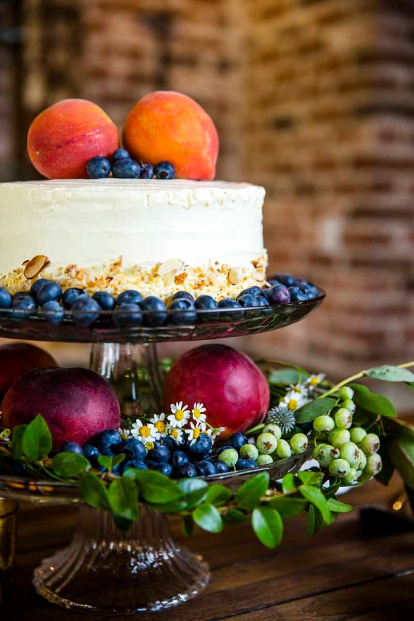 Cake on vintage cake stand with blueberries and peaches. Wedding Planner Jessica Ormond Events. Photography by Caitlin and Ryan Photography.