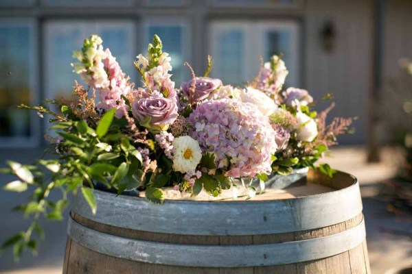 Wine barrel with muted pink and purple flowers for a fall Texas wedding. Floral design by Jessica Ormond Events. Linda McMillan Photography.