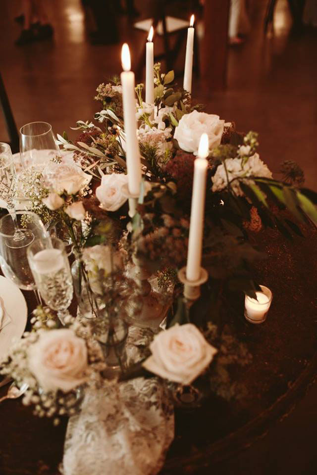 French country inspired sweetheart table with clusters of garden roses and pillar candles. Photo by Lubbock photographer Ashley J Photography. Floral design by Jessica Ormond Events.