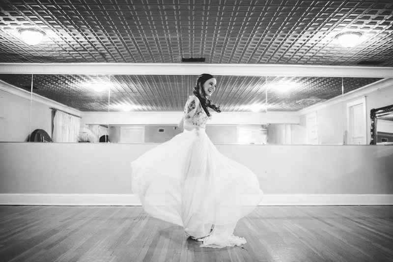 Black and white photo of bride spinning in her dress taken by Photo by Betsy.