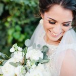 Smiling bride with white bouquet of peonies and eucalyptus designed by Lubbock florist Jessica Ormond Events. Texas photographer Tara Hobgood Photography.