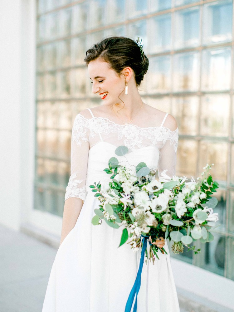 Elegant Texas bride in downtown Lubbock with textured bouquet in green and white.