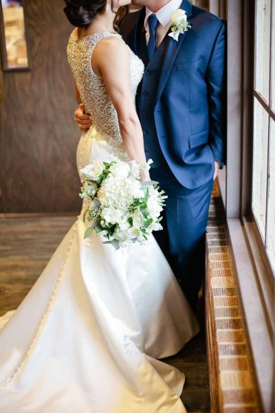White hydrangea bridal bouquet and Lubbock bride and groom for winter ceremony. Designed by wedding florist Jessica Ormond Events. Photography by Tara Hobgood.