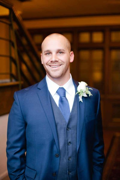 Texas groom with white rose boutonniere in navy suit. Winter wedding at Legacy Event Center in Lubbock. Florist, Jessica Ormond Events. Tara Hobgood Photographer.