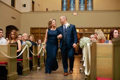 Groom escorting mother to her seat in an elegant winter wedding in Lubbock. Flowers by Texas florist Jessica Ormond Events. Tara Hobgood Photography.
