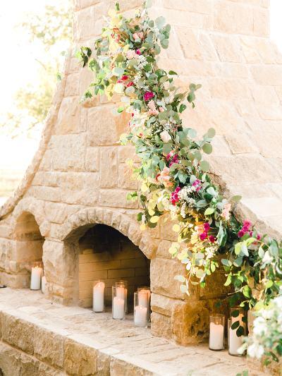 Backyard wedding with flower garland on fireplace.