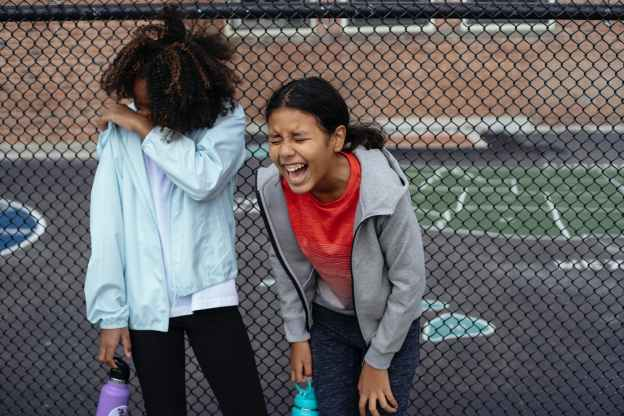 multiethnic schoolgirls laughing on sports ground