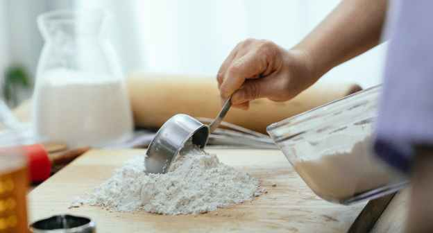 crop adult woman adding flour on wooden cutting board