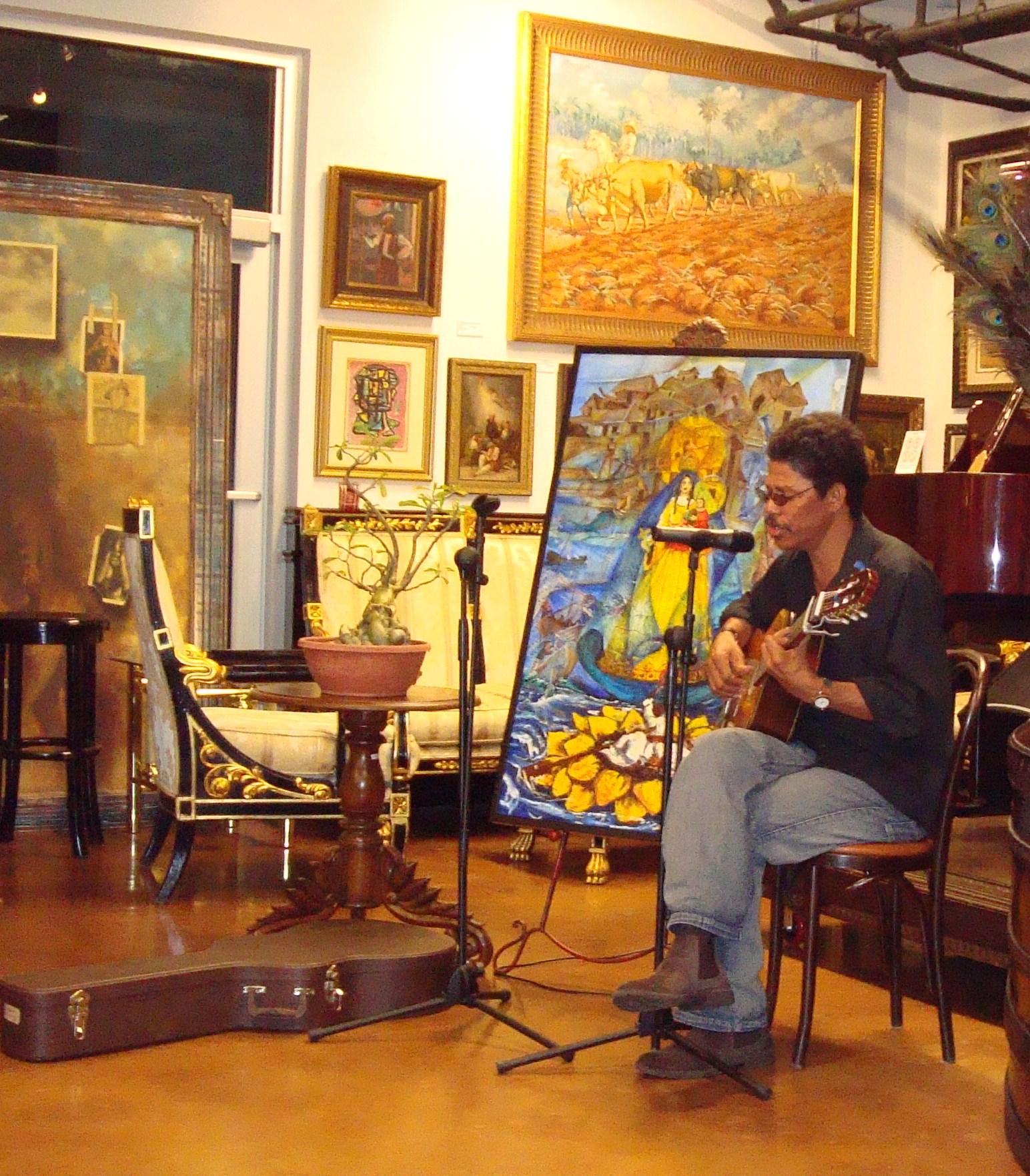 El trovador Alberto Cabrales interpretando sus canciones, junto al cuadro ÉXODO CACHITA, de Ignacio Pérez Vázquez, también presente en la Revista BRUJULAR DE MIAMI, y el Bonsai Babel, de Raúl Ortiz, padre de Melisa.