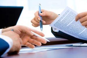 manos con bolígrafos y compartiendo un documento.
