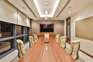 Sala de juntas, con una larga mesa, sillas y una pantalla al fondo, sin personas.
