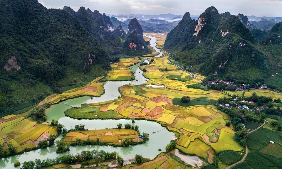 imagen aérea de un paisaje de montañas, ríos y campos sembrados.