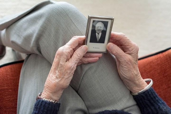manos de una mujer persona mayor, deteniendo un pequeño marco con una foto en blanco y negro de un hombre. Dando la idea de un recuerdo de un ser querido.