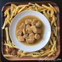 Pollo en salsa de cerveza y cebolla acompañado de patatas fritas
