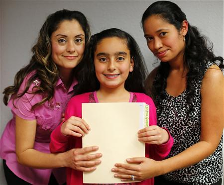 Teresa Villanueva (L) and her 11-year-old daughter Laritza receive help on their charter school application from Barrio Logan College Institute counselor Jennifer Pena (R) in San Diego