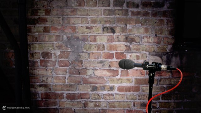 A brick wall lit with a microphone in front.