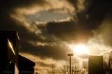 Sun Shining Through Clouds Beside Building