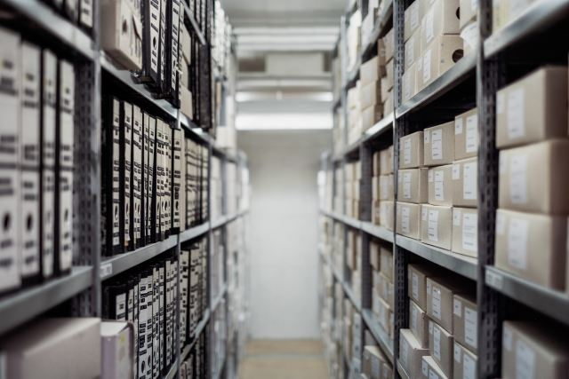 Binders and boxes on shelves in a large archive