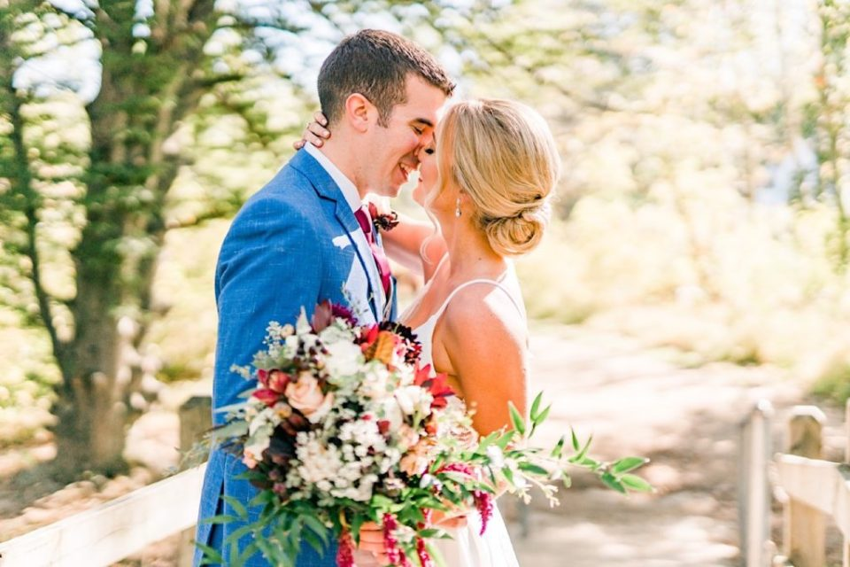 Bride and Groom with a Maroon and green bouquet by Jill Lewko at Philander Chase Knox Estate in Valley Forge