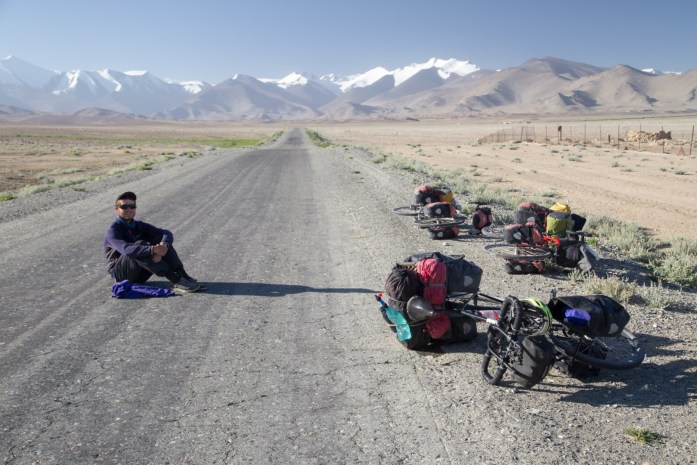 Cyclist sitting in the middle of the road on the Pamir Highway with no cars.