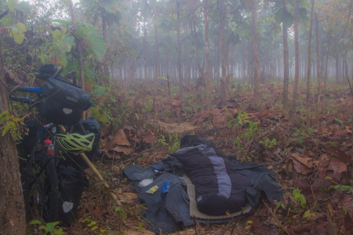 Illegal wild camping in a forest in Myanmar. Sleeping bag on the floor and touring bike beside.