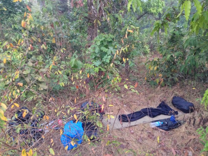 Illegal wild camping in Myanmar. Sleeping bag laid out in the jungle and touring bike laying down.