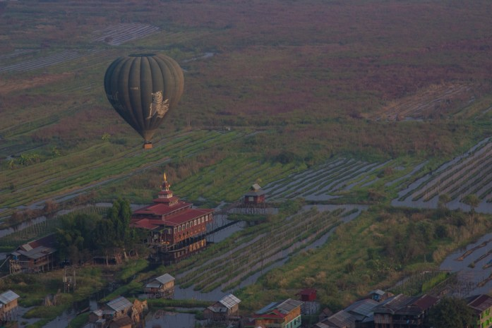 A hot air balloon above a floating monastery on stilts in Inle Lake, Myanmar.