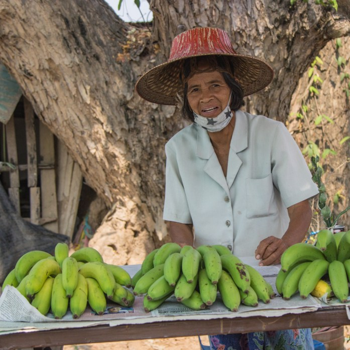 Women in Thailand sells bananas by the side of the road. She wears a traditional hat.