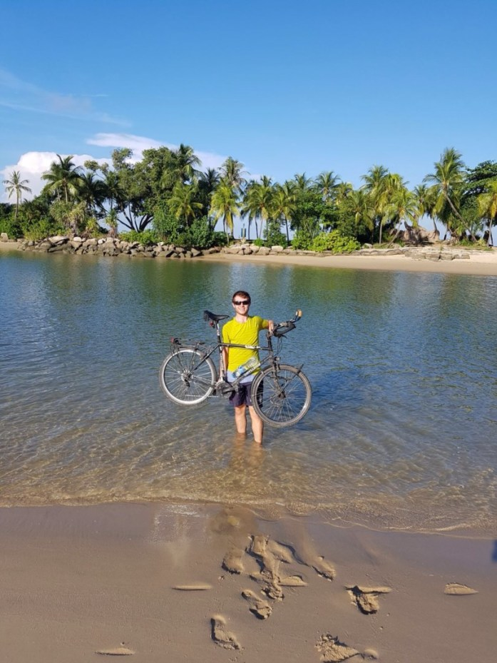 Standing in the sea holding my bike at the southernmost point of continental asia in Singapore.