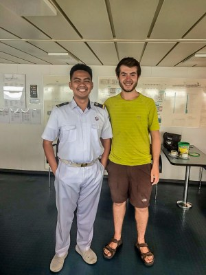 Tourist in Indonesia posing with the Officer driving the Pelni ferry