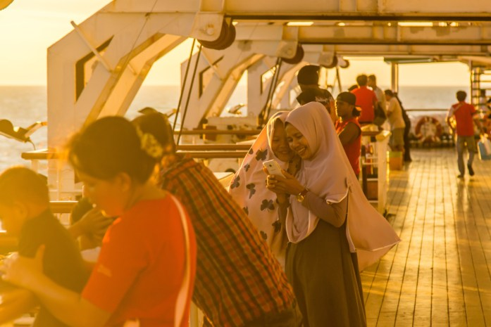 Two beautiful girls with hijab take a selfie on a Pelni ferry in Indonesia at sunset.