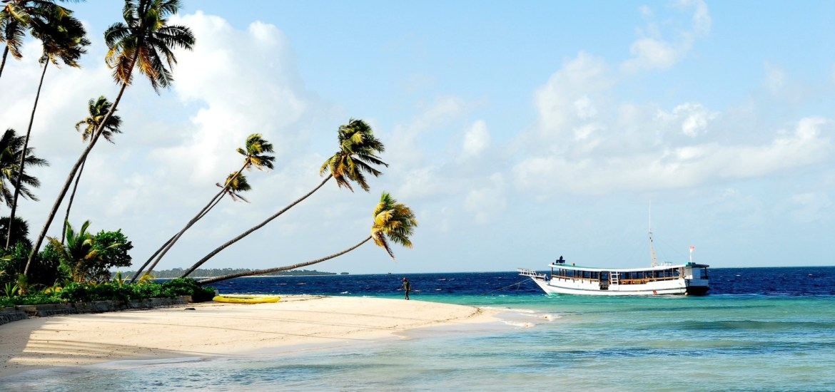 Boat resting by palm trees in Indonesia in beautiful clear, blue water.