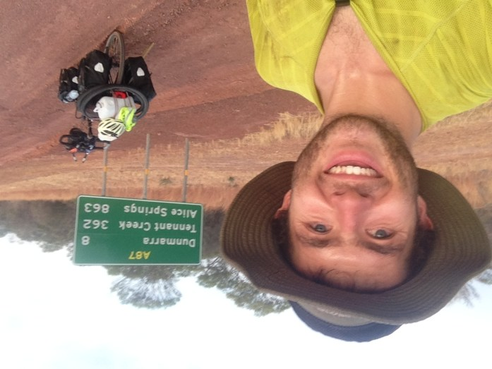 Selfie while bike touring across Australia in front of bicycle and signpost to Alice Springs