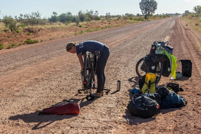 Broken bike problem being fixed on unsealed dirt road in Australian Outback