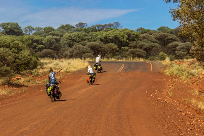 Bicycle Tourers reach the end of the dirt road and cycle onto sealed road again in Australia Outback