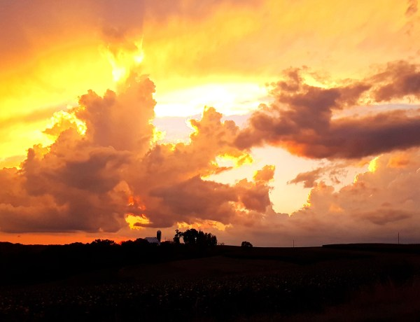 Beautiful sunset of yellow, orange, and red behind a large cloud and a farm in silhouette.
